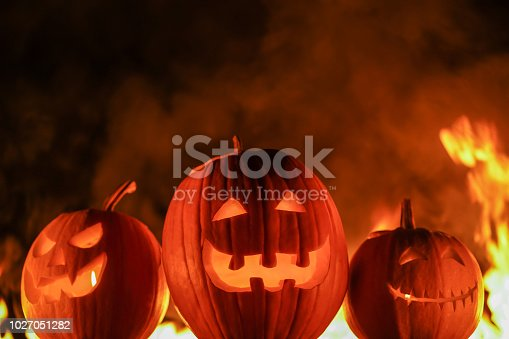 Terrifying symbols of Halloween - Jack-o-lanterns. Scary carved halloween pumpkins on black flaming fire background. All Hallows' Eve or All Saints' Eve.