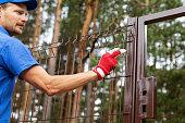 territory enclosure - worker installing metal fence