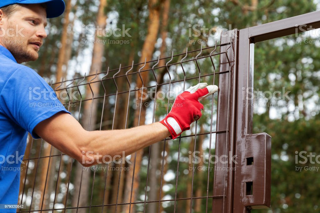 territory enclosure - worker installing metal fence stock photo