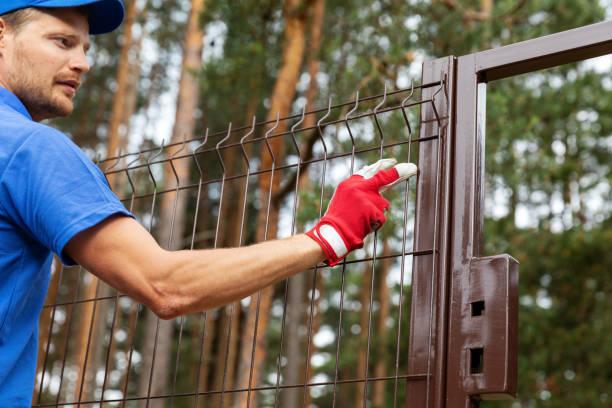 territory enclosure - worker installing metal fence - staccionata foto e immagini stock