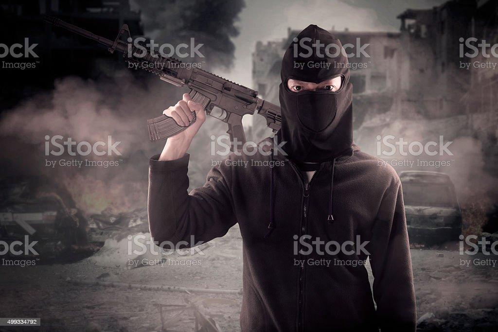 Terrorist carrying rifle at broken city stock photo