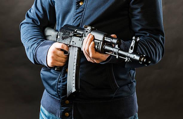 terrorist holding kalashnikov rifle stock photo
