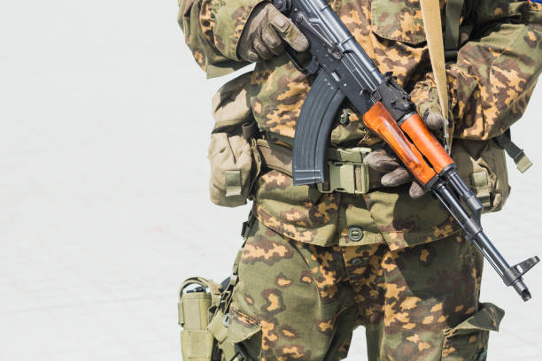 Terrorist military solder guard uniform holding AK gun with space for text stock photo