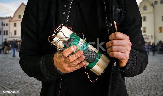 Dangerous terrorist on street with a lot of people and dynamite bomb in hand - terrorism concept