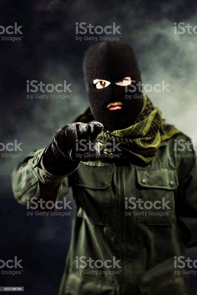 Terrorist pointing to camera and threatening stock photo