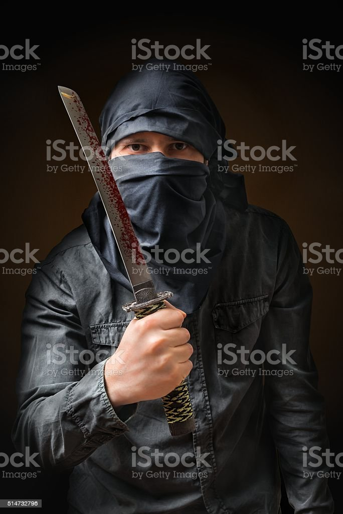 Terrorist threatening with bloody knife. Low key photo. stock photo
