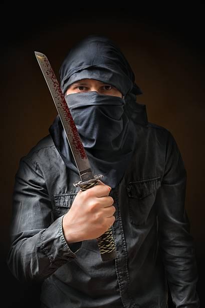terroristischen bedrohung mit blutigen messer. low schlüssel bild. - hackmesser stock-fotos und bilder