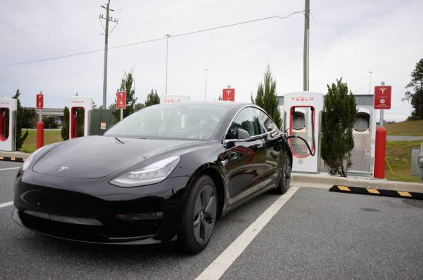 Tesla car at supercharger station near interstate stock photo