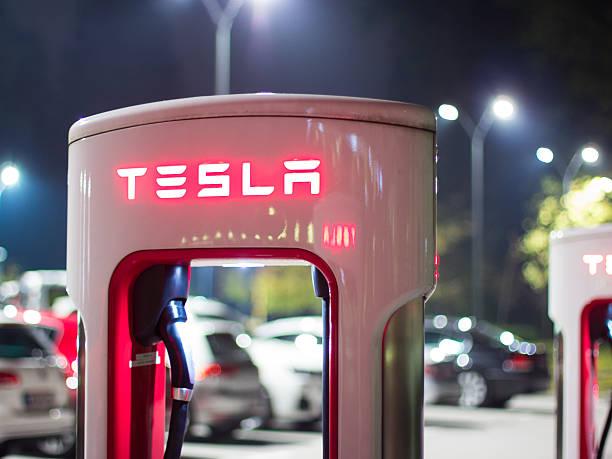 Tesla car charger at night Ljubljana, Slovenia - October 13, 2016: Tesla car supercharger machine at Supercharger Station glowing at night tesla motors stock pictures, royalty-free photos & images