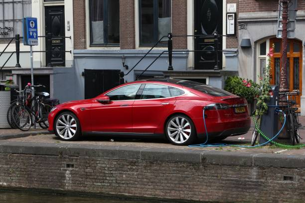 Tesla car charging Electric Tesla Model S car charged by the canal in Amsterdam. Netherlands has 528 registered cars per 1,000 inhabitants. tesla model s stock pictures, royalty-free photos & images