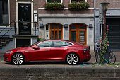 Electric Tesla Model S car parked by the canal in Amsterdam. Netherlands has 528 registered cars per 1,000 inhabitants.