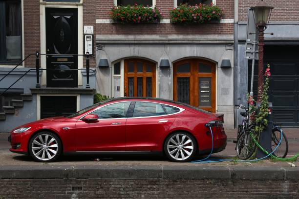 Tesla car Electric Tesla Model S car parked by the canal in Amsterdam. Netherlands has 528 registered cars per 1,000 inhabitants. tesla motors stock pictures, royalty-free photos & images