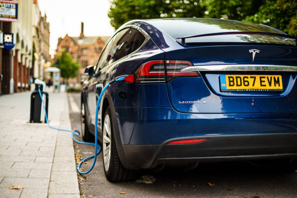 Tesla Charging on street in Coventry UK. Coventry, UK - August 31, 2018: Coventry City Centre Tesla electric vehicle parking area and charging from street electrical dock. tesla motors stock pictures, royalty-free photos & images