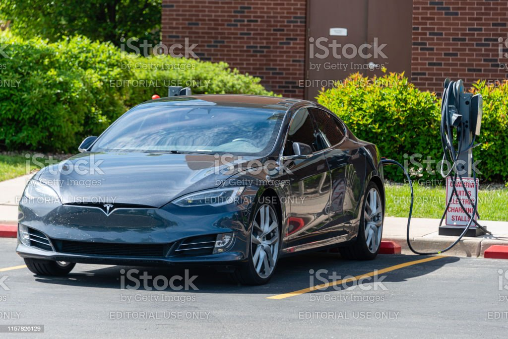 Tesla Charging Station Tesla electric car being charged at a charging station located in the parking lot of a Cambria Suites hotel in Fort Collins, Colorado. 2019 Stock Photo