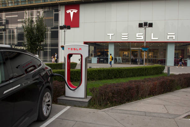 Tesla Charging Station Beijing, China - July 17, 2019: A Tesla electric car is being charged at a Tesla charging station outside a Tesla store in SPK Beijing, a high-end shopping center in Beijing's Chaoyang District. tesla motors stock pictures, royalty-free photos & images