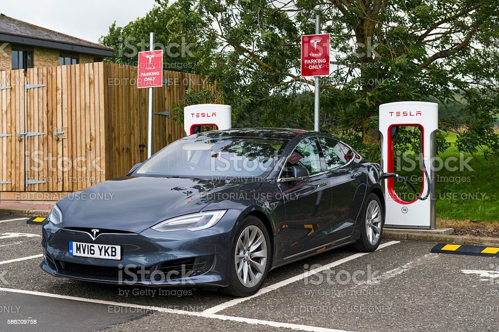 Tesla electric car plugged into a charging station stock photo