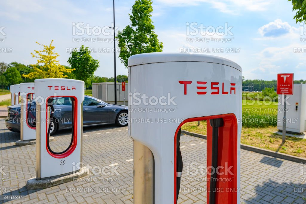 Tesla electric car supercharger charging station at a parking lot...