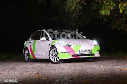 Berlin, Germany - 7th October, 2019: Tesla Model 3 stopped on the street at night. The Model 3 is the most popular electric car in the world. Light painting image.