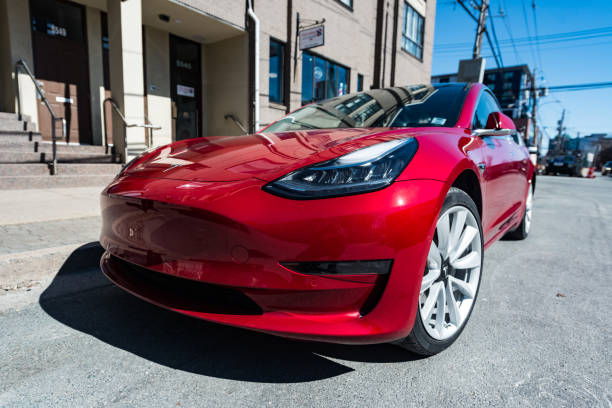 Tesla Model 3 March 26, 2019 - Halifax, Canada - A 2019 red Tesla Model 3 plug-in electric car parked on a city street in downtown Halifax. tesla motors stock pictures, royalty-free photos & images