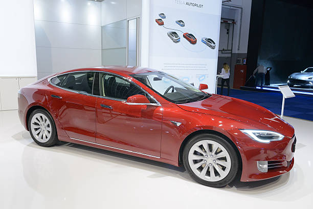 Tesla Model S 75D all-electric luxury saloon car side view Brussels, Belgium - January 13, 2017: Tesla Model S 75D all-electric, luxury, saloon car during the 2017 European Motor Show Brussels.The Model S is one of the world's top selling plug-in electric cars and this 75D is fitted with All Wheel Drive and autopilot. The car is displayed on a motor show stand, with lights reflecting off of the body. There are people looking around and other cars on display in the background. tesla model s stock pictures, royalty-free photos & images