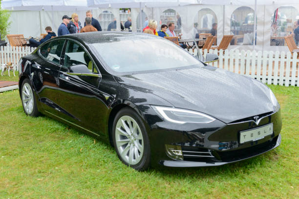 Tesla Model S all-electric luxury saloon car Tesla Model S  all-electric, luxury, saloon car in black. The Model S is one of the world's top selling plug-in electric cars and is fitted with All Wheel Drive and autopilot. The car is on display during the 2017 Classic Days at Schloss Dyck. People in the background are looking at the cars. tesla model s stock pictures, royalty-free photos & images