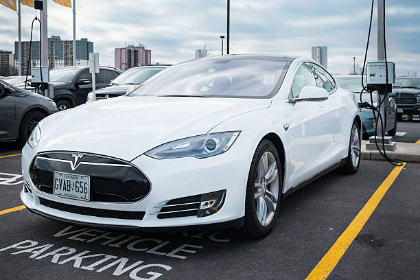 Tesla Model S at Charging Station Burlington, Canada - February 29, 2016: A white colored Tesla Model S electric car being charged at a parking lot in Burlington, Ontario. tesla model s stock pictures, royalty-free photos & images
