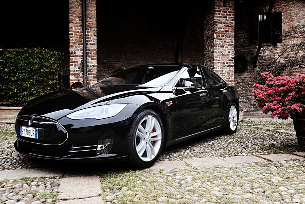 Tesla model S car parked in old  Milan , Italy - April  21, 2016 : tesla model S car parked in old farm courtyard in Milan,Italy tesla model s stock pictures, royalty-free photos & images