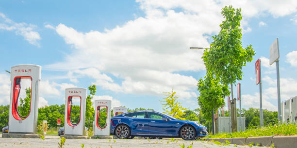 Tesla Model S electric car at a supercharger charging station Black Tesla Model S electric car at a supercharger charging station. Superchargers are free connectors that charge Model S in minutes. Superchargers are used for long distance travel,  located along the most popular routes in North America, Europe and Asia. tesla model s stock pictures, royalty-free photos & images