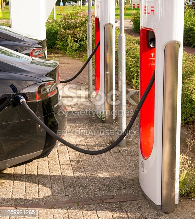 Black Tesla Model S electric car at a supercharger charging station. Superchargers are free connectors that charge Model S in minutes. Superchargers are used for long distance travel,  located along the most popular routes in North America, Europe and Asia.