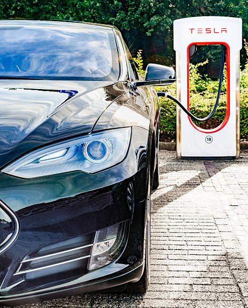 Tesla Model S electric car at a supercharger charging station Zevenaar, The Netherlands - September 10, 2015: Black Tesla Model S electric car at a Tesla supercharger charging station. tesla model s stock pictures, royalty-free photos & images