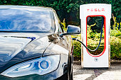Zevenaar, The Netherlands - September 10, 2015: Black Tesla Model S electric car at a Tesla supercharger charging station. Superchargers are free connectors that charge Model S in minutes. Superchargers are used for long distance travel, located along the most popular routes in North America, Europe and Asia.