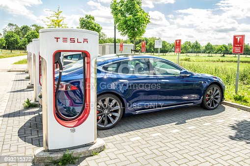 Tesla Model S electric car at a supercharger charging station. Superchargers are free connectors that charge Model S in minutes. Superchargers are used for long distance travel, located along the most popular routes in North America, Europe and Asia.