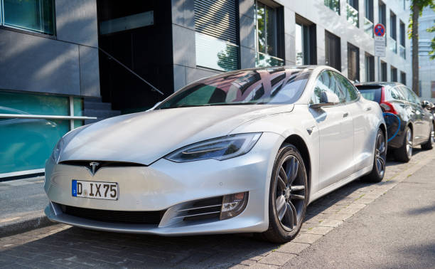 Tesla Model S electric car at the Media Harbour Duesseldorf, Germany- August 26. 2019: A silver Tesla Model S is parked beside the street in the Media Harbour Duesseldorf and is connected with a blue power chord to a recharging station. tesla model s stock pictures, royalty-free photos & images