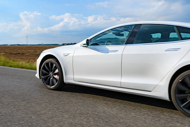 Tesla Model S full electric luxury car driving Jüchen, Germany - August 5, 2016: White Tesla Model S full electric luxury car driving past on a country road. The Tesla Model S is a full-sized plug-in electric five-door, luxury liftback, produced by the American automotive company Tesla Motors. tesla model s stock pictures, royalty-free photos & images