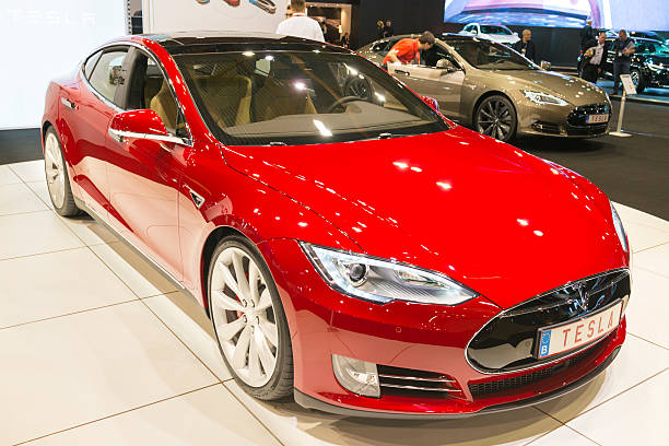 Tesla Model S full electric luxury car Brussels, Belgium - Januari 12, 2016: Red Tesla Model S full electric luxury car front view. The car is on display during the 2016 Brussels Motor Show. The car is displayed on a motor show stand, with lights reflecting off of the body. There are people looking around and other cars on display in the background. tesla model s stock pictures, royalty-free photos & images