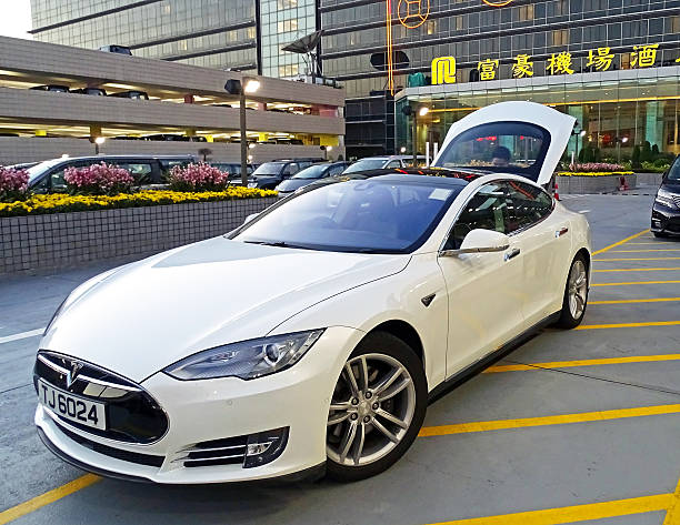 Tesla Model S in Hong Kong Chek Lap Kok, Hong Kong - February 8, 2016: An electric vehicle Model S of the brand Tesla Motors parked at the airport in Chek Lap Kok, Hong Kong. The driver loads the luggage of passengers in the trunk, who booked the car for airport transfer. In the background, the Regal Airport Hotel can be seen. tesla model s stock pictures, royalty-free photos & images