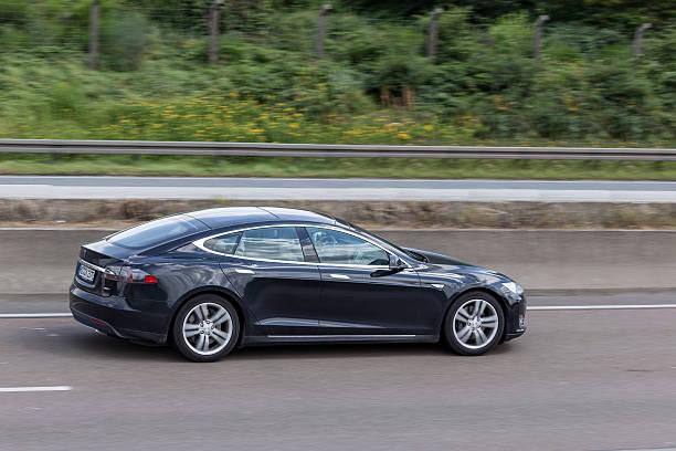 Tesla Model S on the highway Frankfurt, Germany - July 12, 2016: Black Tesla Model S luxury electric sedan on the highway   tesla model s stock pictures, royalty-free photos & images