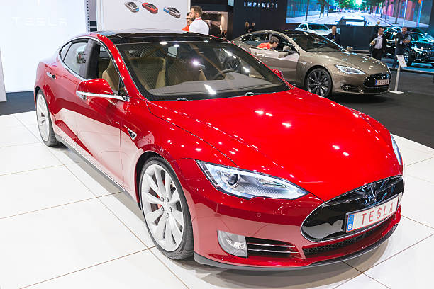 """Tesla Model S P90D full electric luxury car Brussels, Belgium - Januari 12, 2016: Red Tesla Model S P90D full electric luxury car front view. The P90D is fitted with All Wheel Drive and combines a front and rear axle power to a total of 762 horsepower for a 0-€""""60 mph time of 2.8 sec. The car is on display during the 2016 Brussels Motor Show. The car is displayed on a motor show stand, with lights reflecting off of the body. There are people looking around and other cars on display in the background. tesla model s stock pictures, royalty-free photos & images"""