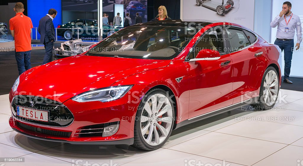 "Tesla Model S P90D full electric luxury car Brussels, Belgium - Januari 12, 2016: Red Tesla Model S P90D full electric luxury car front view. The P90D is fitted with All Wheel Drive and combines a front and rear axle power to a total of 762 horsepower for a 0-€""60 mph time of 2.8 sec. The car is on display during the 2016 Brussels Motor Show. The car is displayed on a motor show stand, with lights reflecting off of the body. There are people looking around and other cars on display in the background. 2016 Stock Photo"