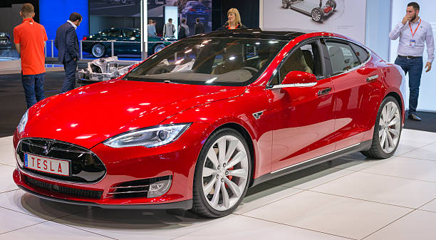 """Tesla Model S P90D full electric luxury car Brussels, Belgium - Januari 12, 2016: Red Tesla Model S P90D full electric luxury car front view. The P90D is fitted with All Wheel Drive and combines a front and rear axle power to a total of 762 horsepower for a 0-€""""60 mph time of 2.8 sec. The car is on display during the 2016 Brussels Motor Show. The car is displayed on a motor show stand, with lights reflecting off of the body. There are people looking around and other cars on display in the background. tesla motors stock pictures, royalty-free photos & images"""