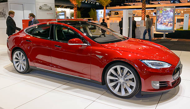 Tesla Model S Brussels, Belgium - January 14, 2014: Red Tesla Model S full-sized electric five-door hatchback on display at the 2014 Brussels motor show. People in the background are looking at the cars. 2014 stock pictures, royalty-free photos & images