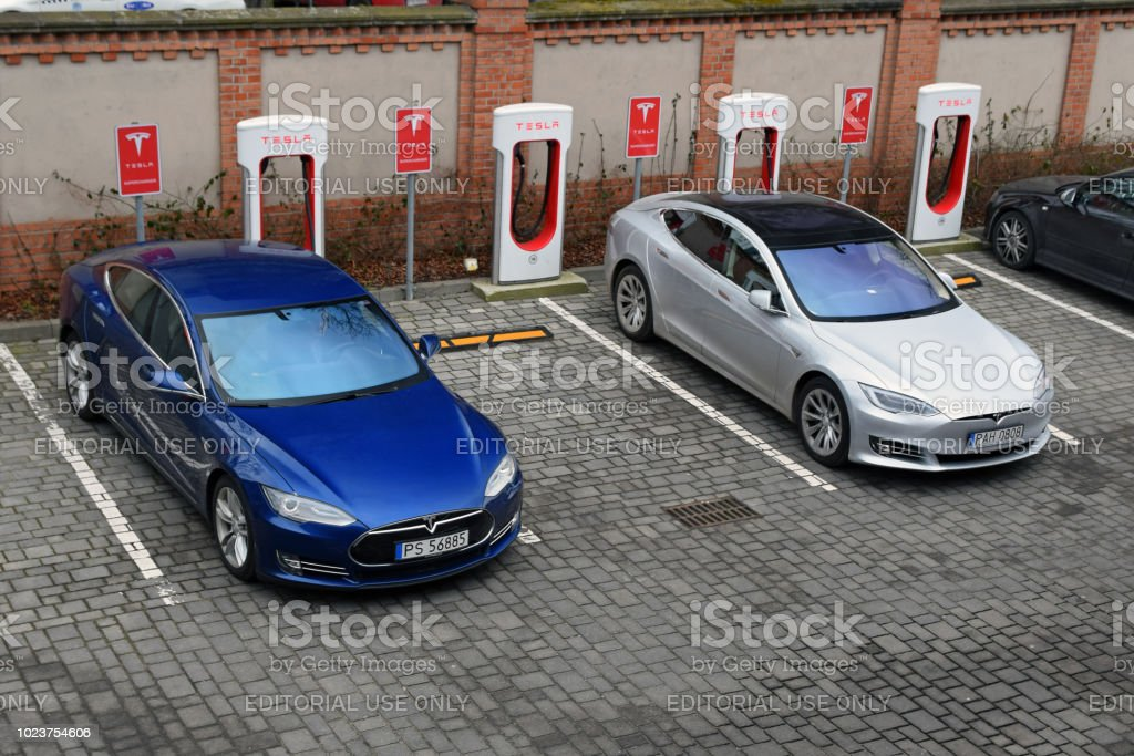 Tesla Model S vehicles on the electric charging point Poznan, Poland - 15th February, 2018: Supercars Tesla Model S parked on the public Tesla Supercharger charging point. Tesla Model S is one of the most popular electric vehicles in Europe. 2018 Stock Photo