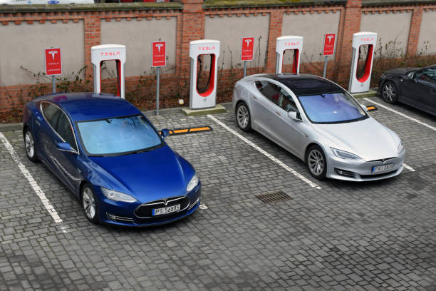 Tesla Model S vehicles on the electric charging point Poznan, Poland - 15th February, 2018: Supercars Tesla Model S parked on the public Tesla Supercharger charging point. Tesla Model S is one of the most popular electric vehicles in Europe. tesla motors stock pictures, royalty-free photos & images