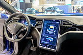 Brussels, Belgium - January 13, 2017: Luxurious interior on a Tesla Model X 90D full electric luxury crossover SUV car with a large touch screen and dashboard screen. The car is fitted with leather seats and aluminium details. The Model X uses falcon wing doors for access to the second and third row seats. The car is displayed on a motor show stand, with lights reflecting off of the body. There are people looking around and other cars on display in the background.