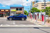 Adelaide CBD, Australia - November 18, 2017: Tesla Model X car and Tesla Supercharger EV charging station in city centre on Franklin Street on a day