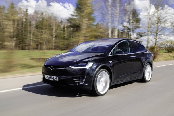 Tesla Model X P90D Minsk, Belarus - April 7, 2017: Tesla Model X P90D on a highway. Model X is the fastest and most capable SUV in history. It accelerates from zero to 60 miles per hour in 3.2 seconds. Tesla Model X equipped with autopilot system matches speed to traffic conditions, keeps within a lane, automatically changes lanes without requiring driver input. tesla motors stock pictures, royalty-free photos & images