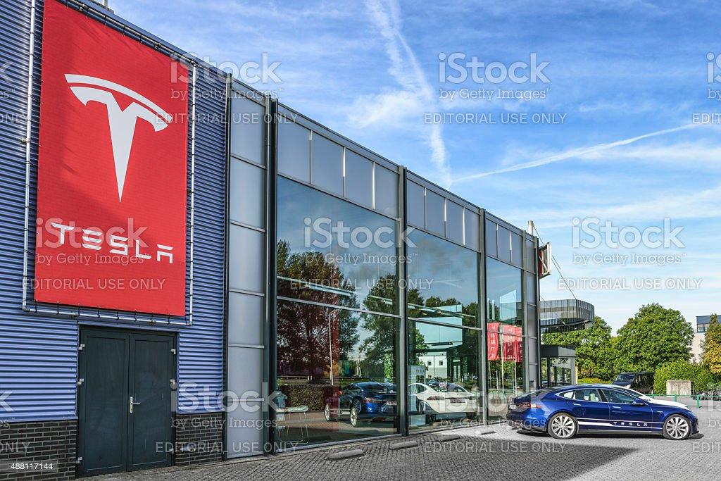Tesla Motors dealership Duiven, The Netherlands - September 10, 2015: Blue and white Tesla Model S full electric luxury car parked outside a dealership.  2015 Stock Photo