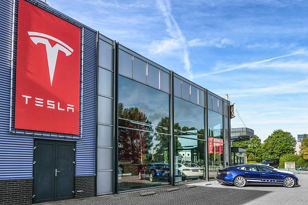 Tesla Motors dealership Duiven, The Netherlands - September 10, 2015: Blue and white Tesla Model S full electric luxury car parked outside a dealership.  tesla motors stock pictures, royalty-free photos & images