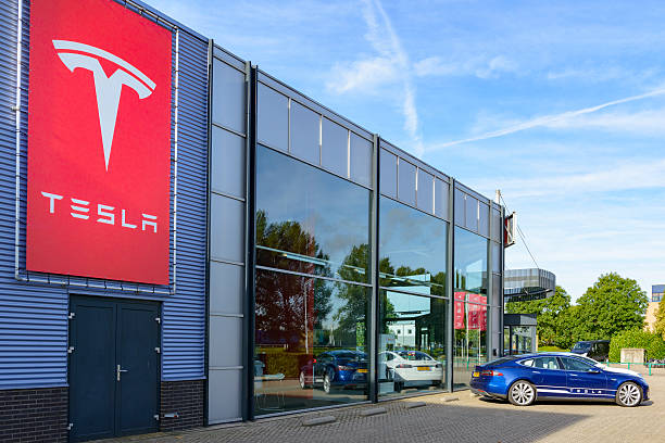 Tesla Motors dealership with a Tesla Model S electric car Duiven, The Netherlands - September 10, 2015: Blue and white Tesla Model S full electric luxury car parked outside a dealership. The Tesla Model S is a full-sized plug-in electric five-door, luxury liftback, produced by the American automotive company Tesla Motors. tesla motors stock pictures, royalty-free photos & images