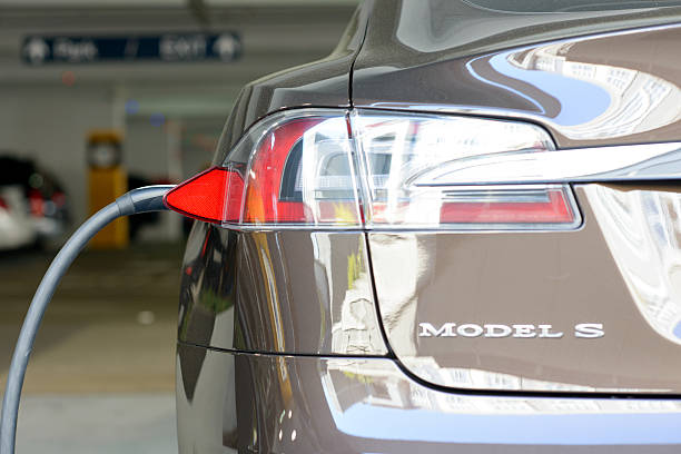 A Tesla Motors Model S charging in San Jose, Calif San Jose, California, USA - March 11, 2013: A Tesla Motors Model S charging at a public parking garage. tesla motors stock pictures, royalty-free photos & images